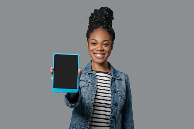 接続されています。手にタブレットを持った浅黒い肌の若い女性の写真