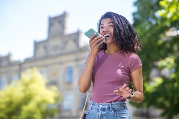 Связаны. довольно улыбающаяся мулатка со смартфоном выглядит довольной и счастливой