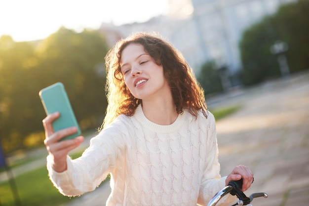 Connected. a young girl in a park with a smartphone in hands