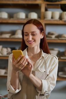Связаны. молодая красивая женщина со смартфоном в гончарной мастерской