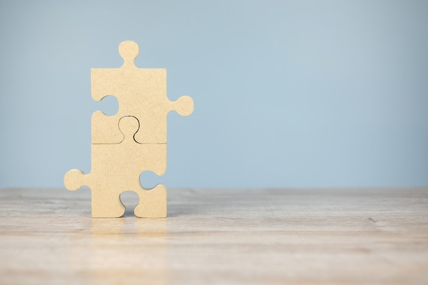 Connecting couple puzzle piece, wood jigsaw on table  . business solutions, mission, success, goals and strategy concepts