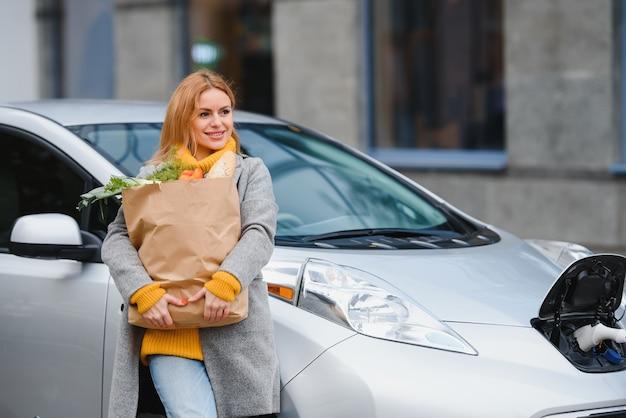 電気自動車の充電プラグを接続する。女の子は電気自動車の近くに立って、車が充電されるのを待ちます。