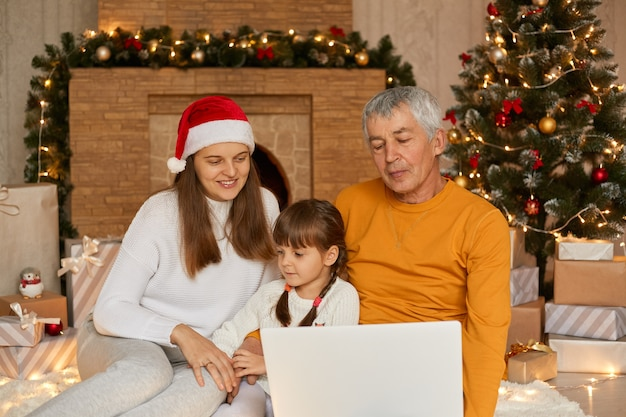 クリスマスイブの間にビデオ通話で家族とつながる、小さな娘と祖父を持つ母親がクリスマスツリーの近くの床に座ってノートパソコンの画面を見ています。
