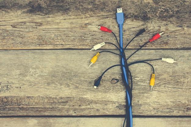 Штепсельные вилки и провода на старом деревянном фоне. тонированное изображение