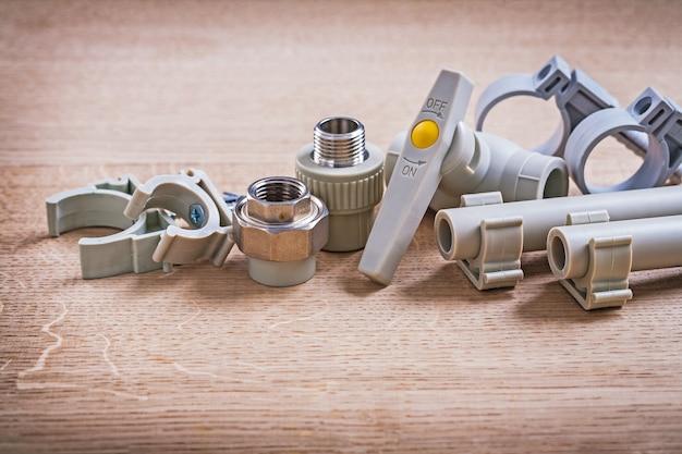 Соединители водяные клапаны полипропиленовые фиксаторы и трубы с зажимами на деревянной доске