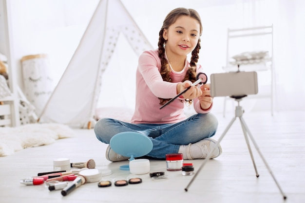 Connoisseur of cosmetics. pleasant cheerful girl reviewing eye shadows for her beauty blog and filming it with a phone while sitting cross-legged on the floor