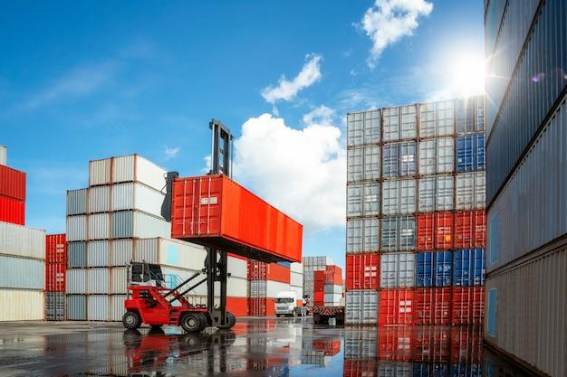 Автомобиль крана перемещает и переносит коробку контейнера от загрузки стога контейнера к тележке в conpany депозита коробки контейнера, это изображение может использовать для концепции дела, логистики, импорта и экспорта.