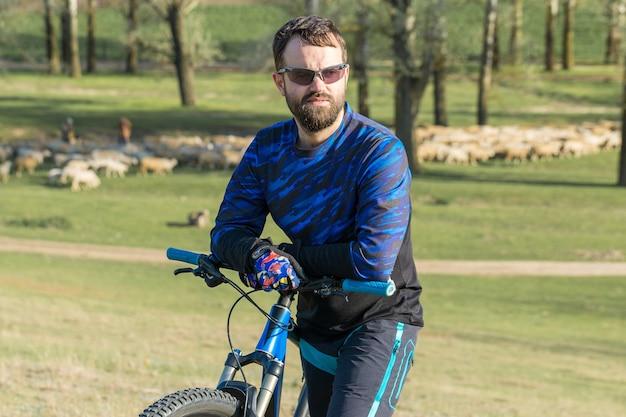 Покорение горных вершин велосипедистом в шортах и майке на современном карбоновом хардтейл-байке с вилкой с пневмоподвеской