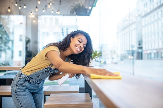 Conscientious worker. young adult smiling woman in denim overalls and tshirt diligently wiping table surface in cafe