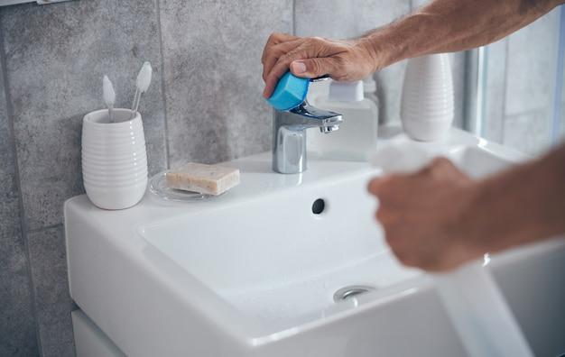자신의 욕실에서 청소하는 동안 클렌징 액체와 수건을 사용하는 의식있는 남자