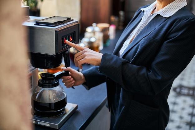 Сознательный офисный работник, стоящий в полуположении во время использования кофеварки