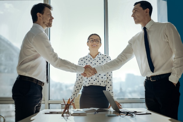 Consensus is reached. handsome young businessmen shaking hands having negotiated a deal while their female colleague looking at them with smile