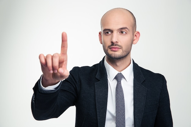 Consentrated handsome young businessman in formalwear  touching copyspace with finger over white wall