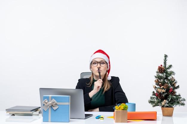 Внимательная блондинка в шляпе санта-клауса сидит за столом с елкой и подарком на ней на белом фоне