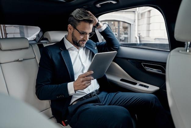 다음 단계를 고려 중입니다. 차에 앉아있는 동안 디지털 태블릿을 사용하여 작업하는 전체 정장에 자신감이 젊은 남자