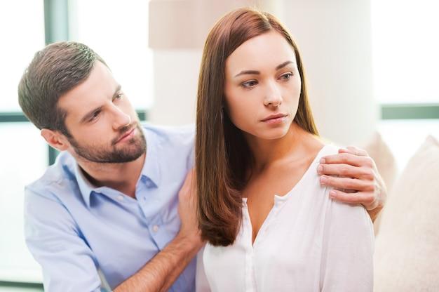 Утешает свою подавленную девушку. подавленная молодая женщина смотрит в сторону, в то время как мужчина сидит позади нее на диване и утешает ее