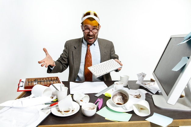 Constant failure. young man spilled drink on the keyboard while working and trying to wake up. drinking a lot of coffee. concept of office worker's troubles, business, problems and stress.