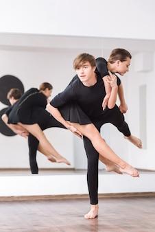 끊임없는 연습. 거울 앞에서 한 발로 서서 발레 댄스 수업을 방문하는 동안 그의 여성 파트너를 잡고 좋은 찾고 좋은 청년