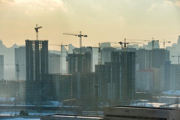 일몰 시 도시에 산업용 크레인이 있는 수축 현장