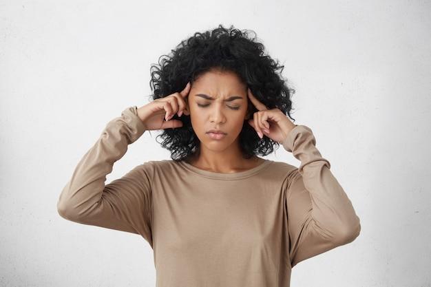 拘束された若い混血の女性が目を閉じて指でこめかみをマッサージする