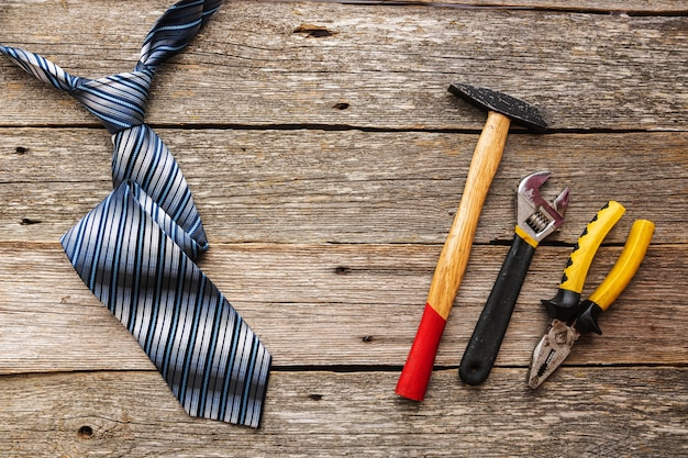 Construccion tools and a tie on wooden background top view