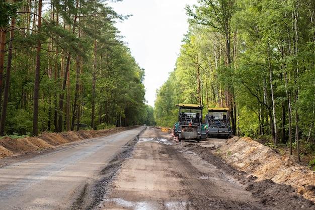Constructing new asphalt roads. modern road repairing equipment near new constructed line of high quality asphalt