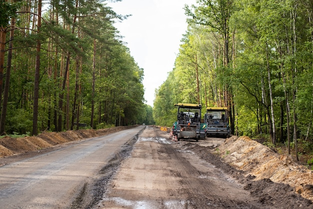 Строительство новых асфальтированных дорог. современная дорожно-ремонтная техника рядом с новой линией высококачественного асфальта.