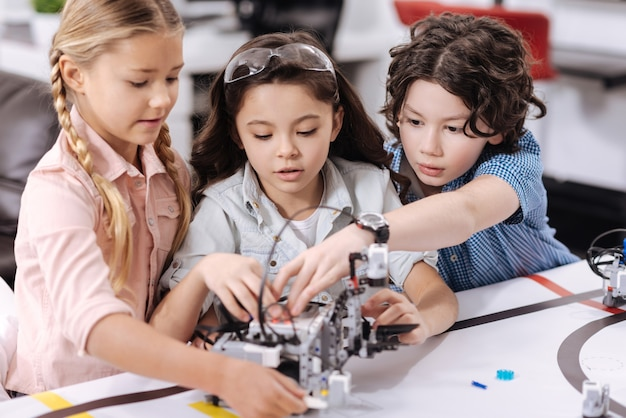 Constructing robot together. skillful friendly smart scientists sitting at school and enjoying class while expressing interest and constructing robot