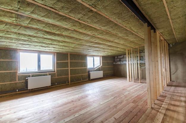 ロックウールで断熱されたオーク材の床、壁、天井を備えた大きな明るく広々とした空の部屋の建設と改修