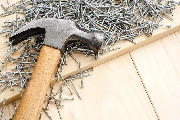 建設と修理。大工仕事。木製のテーブルの上のハンマーとホブネイル