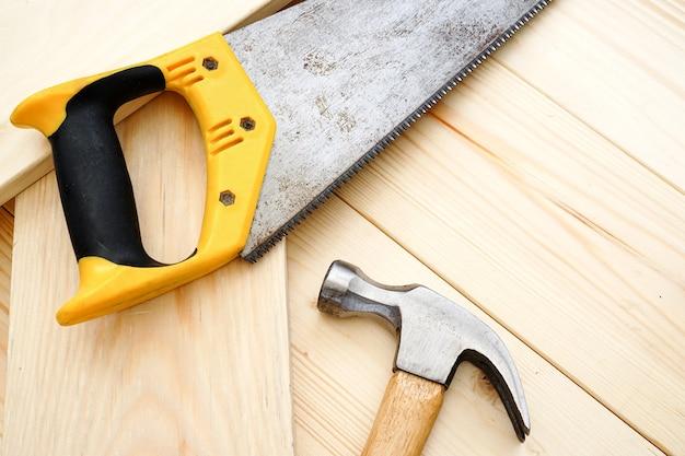 Строительство и ремонт. плотницкие работы. молоток и ржавая пила на деревянном столе