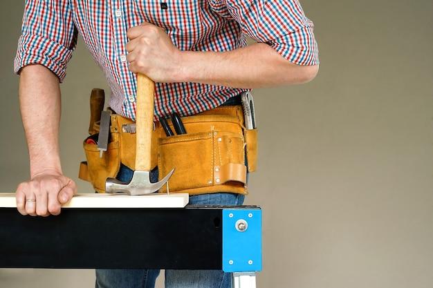 建設と修理。大工仕事。労働者はクローハンマーで釘を抜いています