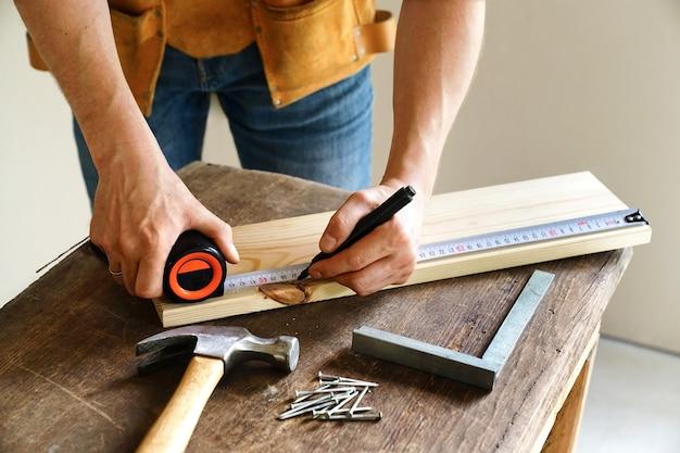 Строительство и ремонт. плотницкие работы. рабочий отмечает доску