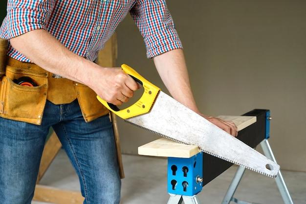 建設と修理。大工仕事。ボードを鋸で切る労働者