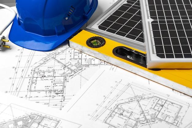 Строительные чертежи каски и солнечной батареи на столе архитекторов