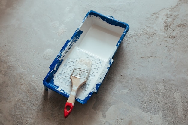 Construction brush in a container of white paint