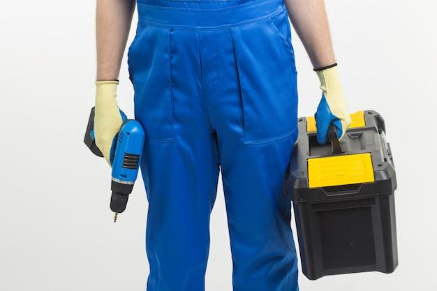 Концепция строительства, строительства и рабочих - красивый строитель, поднимая ящик для инструментов и отвертку на белом фоне.