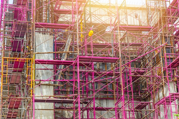 Under construction building covered with scaffolding for safety building structure support.