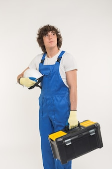 Construction, building and workers concept. curly haired builder lifting up toolbox and white