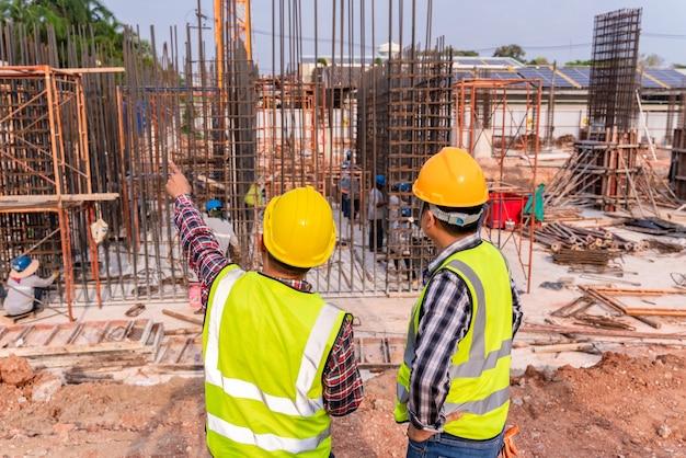 建設現場で進捗状況を監督する建設土木技師および建築家