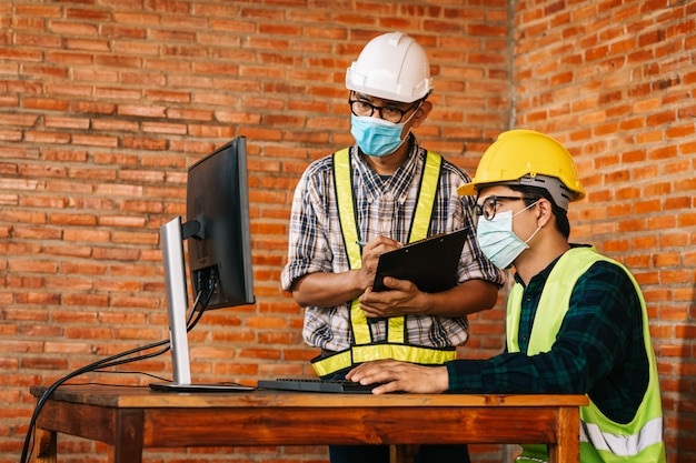 Construction concept of engineer and architect are to wear medical masks working at construction site via monitor for review due to the global impact of covid-19 and social distancing.