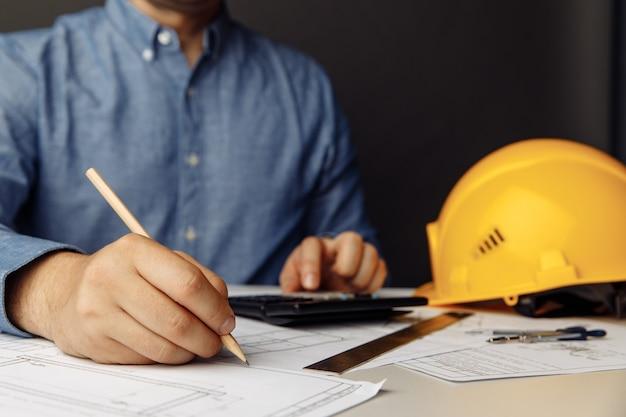 黄色いヘルメット計算機と描画ツールを備えた建設コンセプトエンジニアの職場