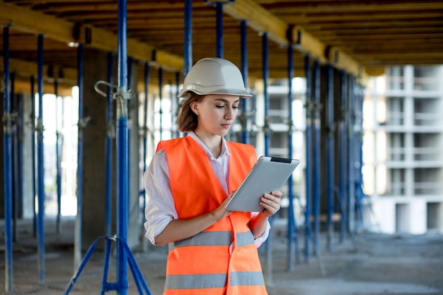 건설 현장에서 일하는 엔지니어 또는 건축가의 건설 개념. 건설 현장에서 태블릿을 들고 있는 여성. 건축국.