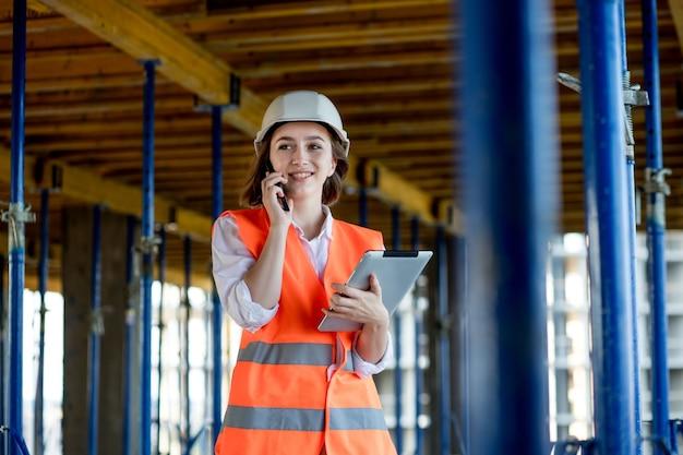 Строительная концепция инженера или архитектора, работающего на строительной площадке. женщина с планшетом на стройке. бюро архитектуры.