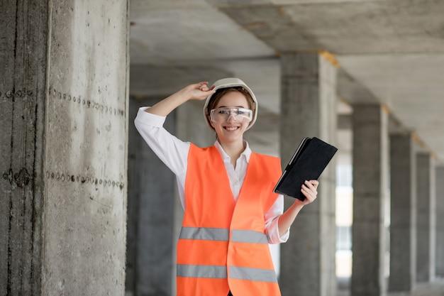 건설 현장에서 일하는 엔지니어 또는 건축가의 건축 개념. 건설 현장에서 태블릿을 가진 여자. 건축 국.