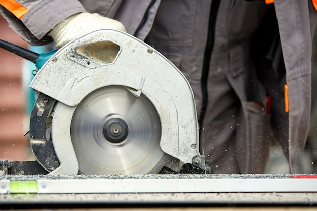 A construction contractor worker using a worm-driven hand-held circular saw to cut boards and plastic. construction , own workshop, hiring a working contract  cutting wood.