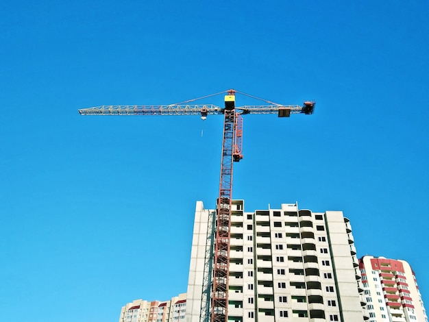 Construction crane at blue sky and unfinished building house