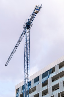 Construction crane and a corner of a new modern building of apartments. construction tecnologies concept.