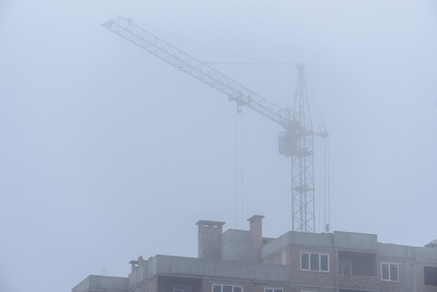 Construction crane in foggy weather on the construction of residential buildings.
