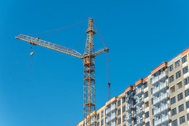 新しい建てられた家の近くの建設用クレーン。建設と開発のコンセプト